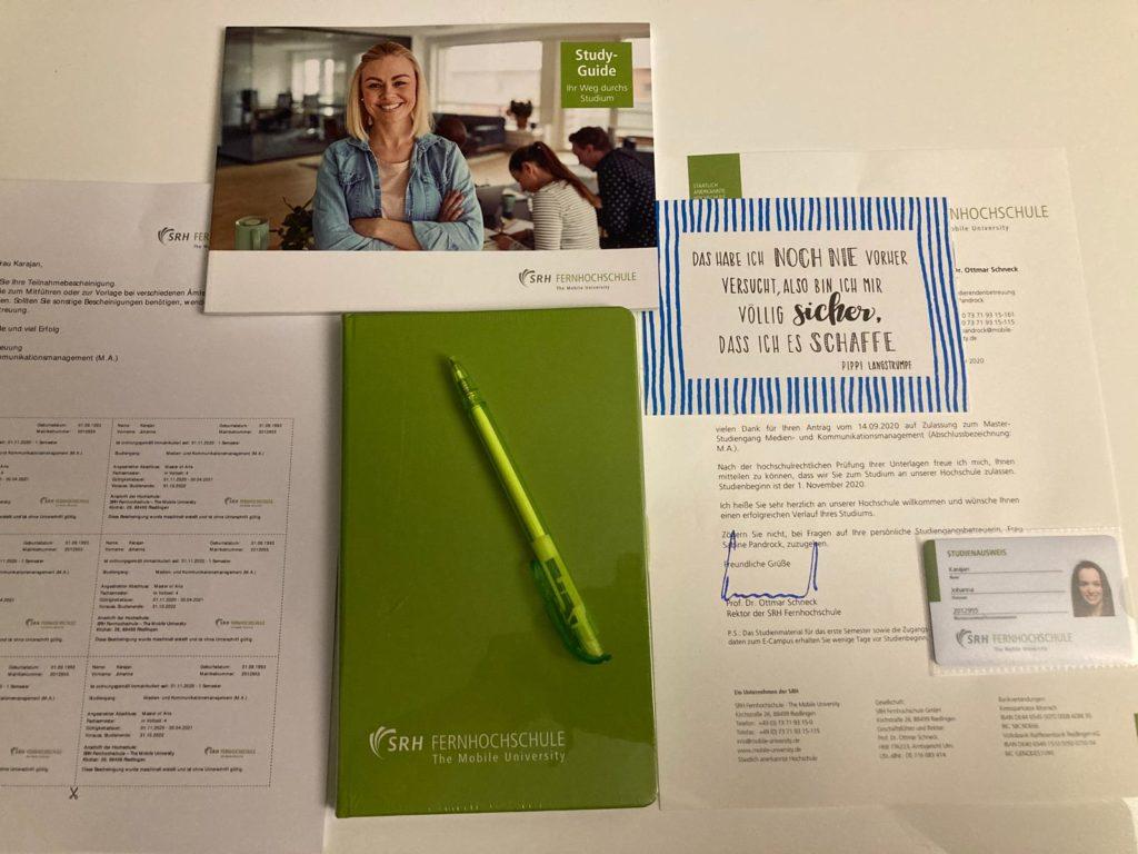 Die Willkommenspost der SRH Fernhochschule enthält einen Block mit Kugelschreiber, die Studienbescheinigung, den Study-Guide und eine motivierende Postkarte.