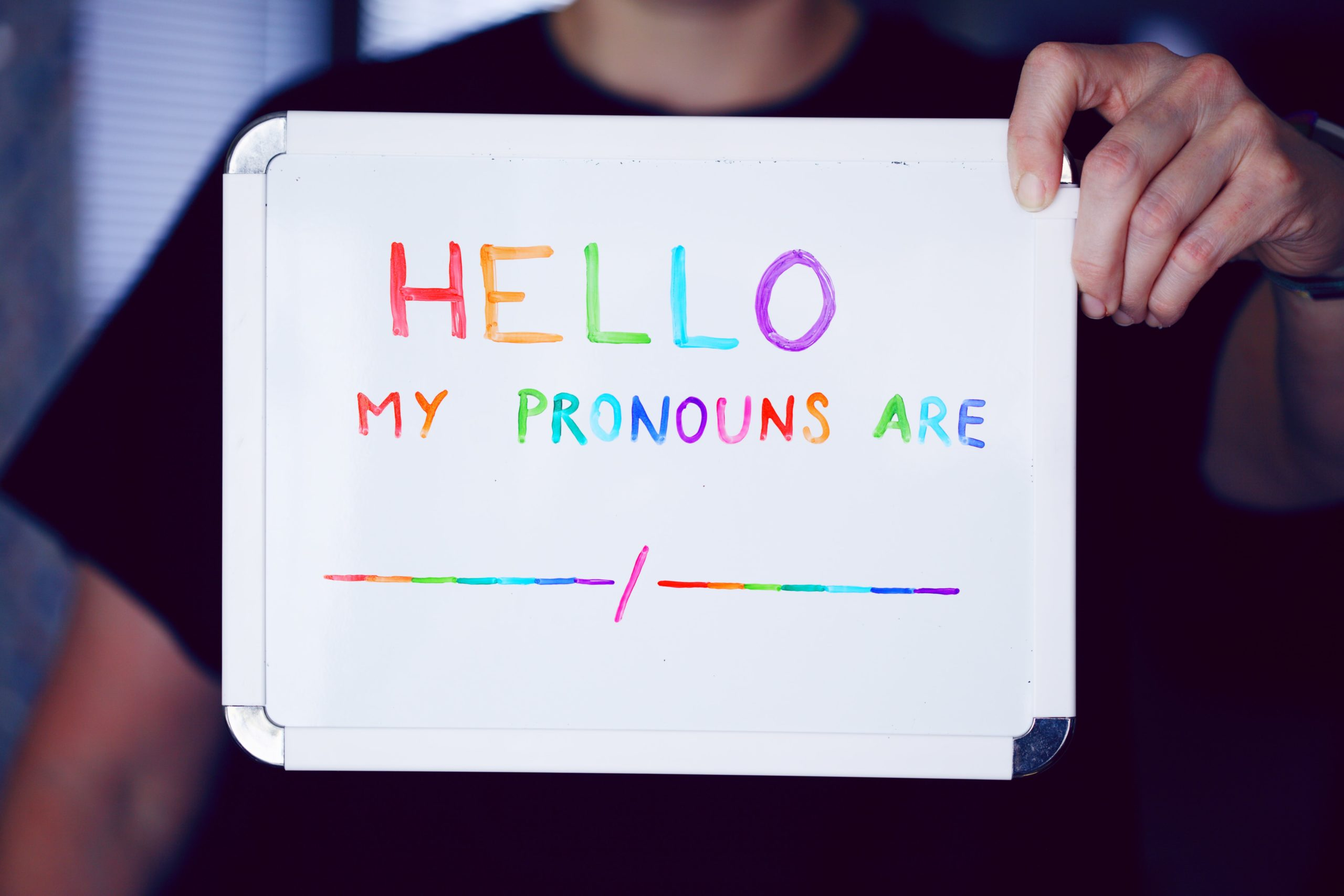 "Person hält Schild ""Hello, My Pronouns are _/_"""