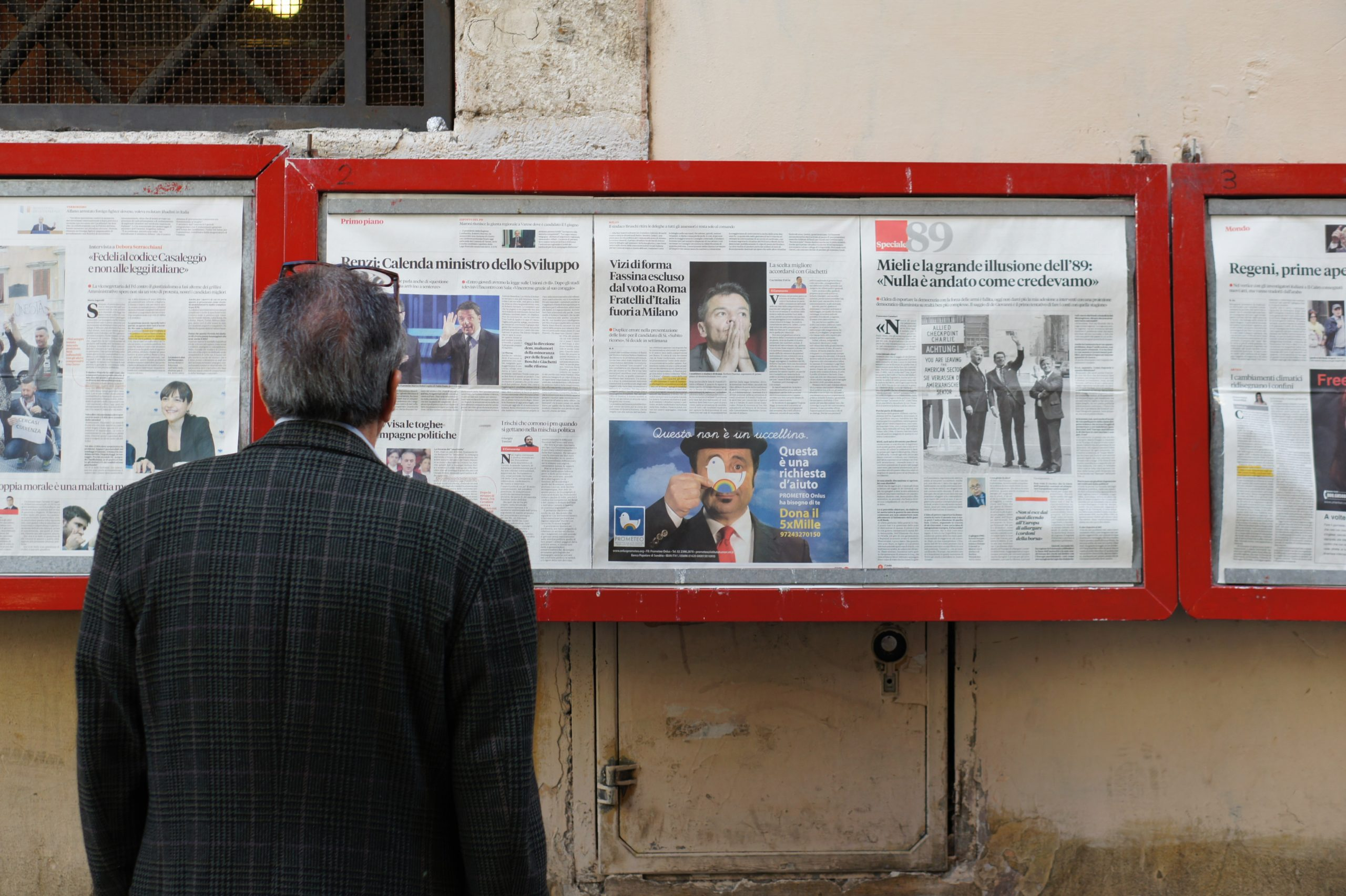Mann vor Zeitungsaushang